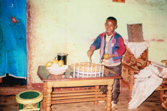 Wondosen, our sponsor child, with food and candles celebrates a church holiday.